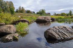 Large boulders on the shore of northern river Royalty Free Stock Photos