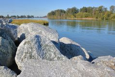 Re-enforcing Riverbank and Shoreline. Large boulders are used to re-enforce a major, wide river and prevent erosion during high water level occurrences Royalty Free Stock Photo