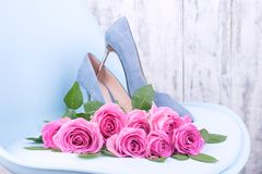 A large bouquet of pink roses on a blue chair in women`s shoes with thin heels. New shoes and flowers. A gift for a woman on royalty free stock photo