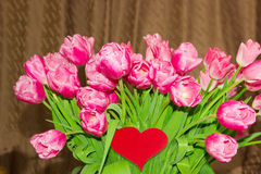 Large bouquet of tulips and heart made of red paper Stock Photos