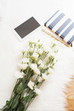 A large bouquet white flowers, notebooks and tablet on the floor on a white fur carpet. Cozy, fashion comfortable femininity home Stock Photo