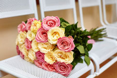 Large bouquet of yellow and pink roses on white chairs Royalty Free Stock Images