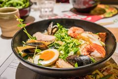 A Bowl of Japanese Ramen. A large bowl of Japanese Ramen with egg, meat, prawn, mussel and vegetable royalty free stock image
