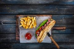 Large bread sandwich with vegetables and roast beef on wooden cutting board stock images
