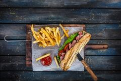 Large bread sandwich with vegetables and roast beef on wooden cutting board royalty free stock image