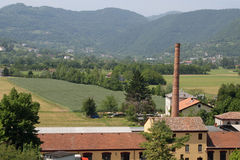 Large brick chimney of a furnace and the hills stock image