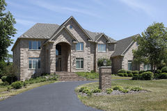 Large brick home with arched entry Stock Photos