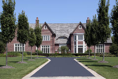 Large brick home with row of trees Royalty Free Stock Photo