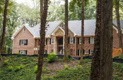 Large Brick Home Under Construction. A large brick home under construction on a wooded lot Royalty Free Stock Photos