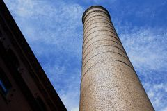 Smokestack in the sky. Large brick smokestack and blue sky from below Royalty Free Stock Image