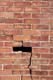 Large brick wall in need of repair, with cracks throughout and sections missing Stock Photography