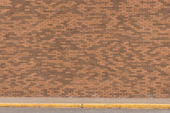 Large Brick Wall with Side walk. Image showing a brick wall with variations in the brick colors from light to dark and a walkway by the road Royalty Free Stock Photo