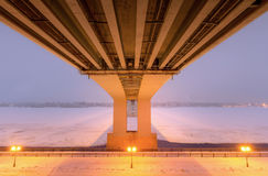 Large bridge over the frozen river. Royalty Free Stock Image