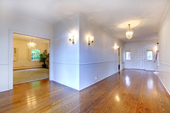 Large bright hallway with hardwood floor and dining room. Royalty Free Stock Photo