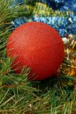 A large bright red ball lies on the New Year`s colored ornaments Royalty Free Stock Photo