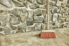 Large broom on wall outdoor - housework Stock Photo