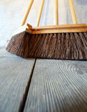 Large brooms on wooden floor housework Royalty Free Stock Image