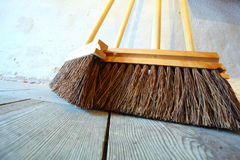 Large brooms on wooden floor housework Royalty Free Stock Photos