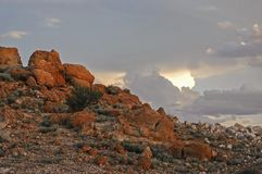Large brown boulders, and dark grey clouds. Large brown boulders on the left and dark grey clouds on the right. Reddish glow on colourful rocks as the sun sets stock photography