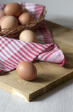 A large brown chicken egg rests on a wooden Board.  Stock Image