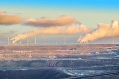 A large brown coal open cast pit mine by Garzweiler in Germany with polluting power plants in the background.  stock images