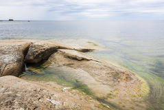 Large brown flat rock in the sea Stock Image