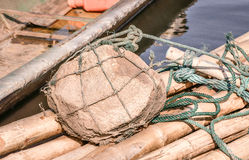 Large brown rock on bamboo boat Stock Image