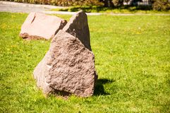 Big brown stones stand in the middle of a bright green lawn stock photos