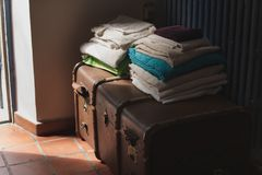 Large brown suitcase stands on floor. Large brown suitcase stands on the floor in the hallway of the house. Towels lie on the closed suitcase Stock Image