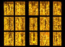 A large brown window with garlands of burning yellow lamps at night from outside. A beautiful large fairy window with dark brown frames and with garlands of royalty free stock photography
