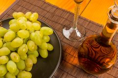Large brush of green grapes in a ceramic plate, a decanter and a glass of wine and cheese. Still life - a large brush of green grapes in a ceramic plate, a royalty free stock images