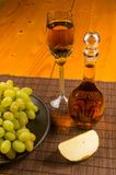 Large brush of green grapes in a ceramic plate, a decanter and a glass of wine and cheese. Still life - a large brush of green grapes in a ceramic plate, a stock photo