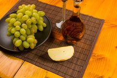 Large brush of green grapes in a ceramic plate, a decanter and a glass of wine and cheese. Still life - a large brush of green grapes in a ceramic plate, a stock images