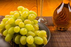 Large brush of green grapes in a ceramic plate, a decanter and a glass of wine and cheese. Still life - a large brush of green grapes in a ceramic plate, a stock photos