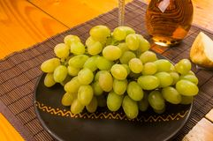 Large brush of green grapes in a ceramic plate, a decanter and a glass of wine and cheese. Still life - a large brush of green grapes in a ceramic plate, a royalty free stock photography