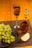 Large brush of green grapes in a ceramic plate, a decanter and a glass of wine and cheese. Still life - a large brush of green grapes in a ceramic plate, a royalty free stock image