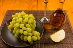 Large brush of green grapes in a ceramic plate, a decanter and a glass of wine and cheese. Still life - a large brush of green grapes in a ceramic plate, a royalty free stock photos
