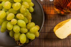 Large brush of green grapes in a ceramic plate, a decanter and a glass of wine and cheese. Still life - a large brush of green grapes in a ceramic plate, a stock image