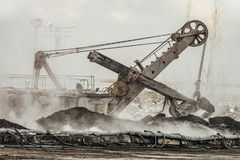 Large bucket excavator works in a hot outdoors dump. Heavy industry. Stock Photos