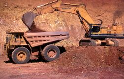 Free Large Bucket Scoop Loads Gold Ore Intoa Giant Dump Truck Royalty Free Stock Photography - 208577647