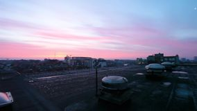 Sunrise over the city. On a large building on the frozen roof with a sunrise over the city stock video footage