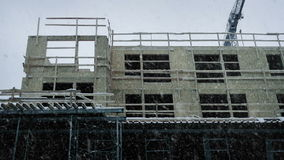 Large Building Under Construction In Snowfall. Building under construction in winter with snow falling stock footage