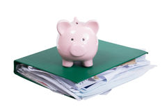 Large bulging office binder with piggy bank. Large bulging office binder full of paperwork with small pink piggy bank on top isolated on white in a conceptual Stock Photos