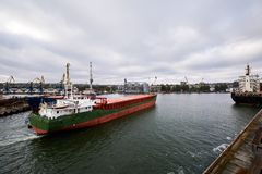 Large bulk ship entering the harbour of commercial dock at seaport to load at grain terminal elevators with wheat and. Large bulk ship entering the harbour of Stock Photos