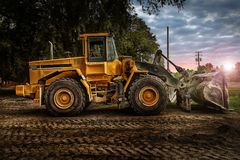 Large bulldozer at construction site, cloudy sky and sunset Stock Images