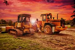 Large bulldozers at construction site, cloudy sky Royalty Free Stock Photo