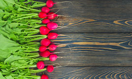 Large bunch of fresh radish on dark boards, closeup Royalty Free Stock Photos