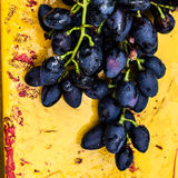 Large bunch of red wine grapes on art painted wooden table. Red Stock Image