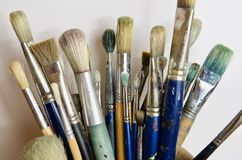 Large bunch of used artist`s paintbrushes upright in a jar. Against a white background Royalty Free Stock Image