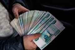 A large bundle of Russian money is squeezed in his hand. royalty free stock photos